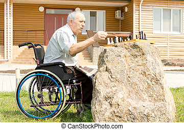 Disabled man playing chess in his garden sitting in his...