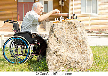 Elderly handicapped man playing chess