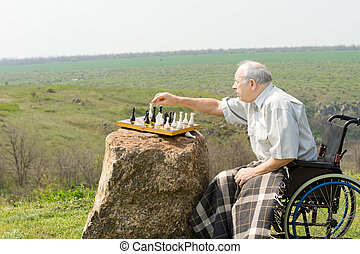 Elderly man in a wheelchair playing chess