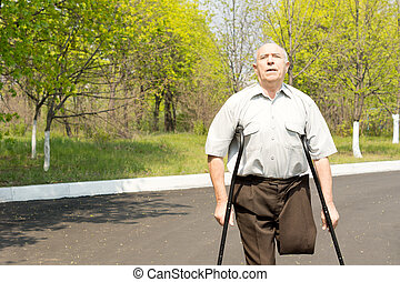 Elderly male amputee balanced on crutches in a rural street...