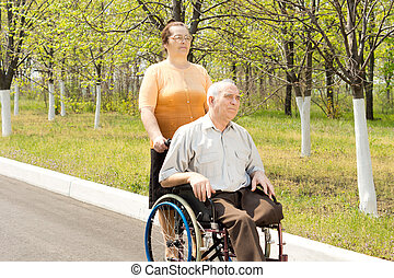 Amputee being taken for a walk in a wheelchair