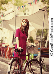 Redhead girl with bike at outdoor, city