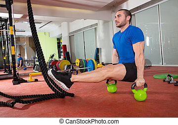 Crossfit fitness man L-sits Kettlebells L sits exercise at...