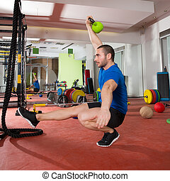 Crossfit fitness man balance Kettlebells with one leg...