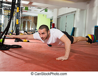 Crossfit fitness man balance pus ups with one leg and arm