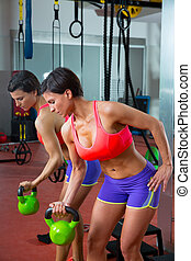 Crossfit fitness lifting Kettlebell woman at mirror workout...