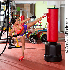 Crossfit woman kick boxing with red punching bag - Crossfit...