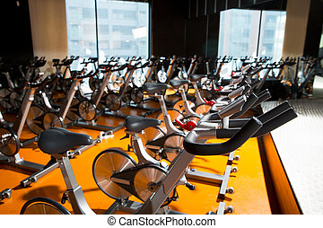 Aerobics spinning exercise bikes gym room in a row -...