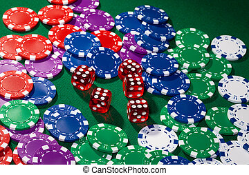 Colorful poker chips and red dice on green cloth