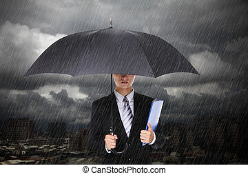 Businessman under heavy rain with storm cloud and city...