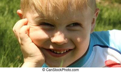 Smiling blond boy on a background o