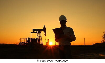 Man engineer with securities for the oil pumping unit sunset...