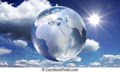 Spinning glass planet Earth on sky background - looped...