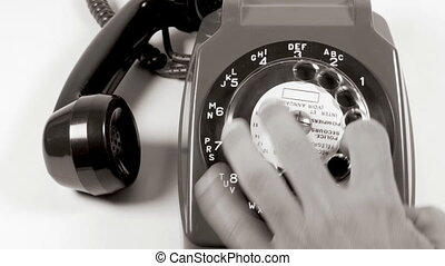 close up of a hand ringing a number on an old fashioned telephone