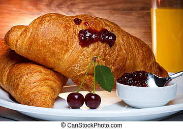 Fresh baked croissants with cherry jam and juice