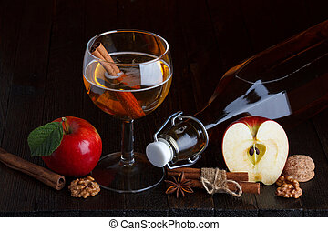 apple cider still life with cinnamon stick, apple, walnut,...