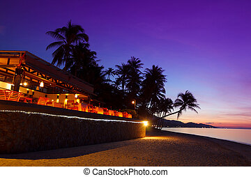 Restaurant at tropical beach with coconut palms during sunset