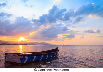 Small fishermans boat at sunset