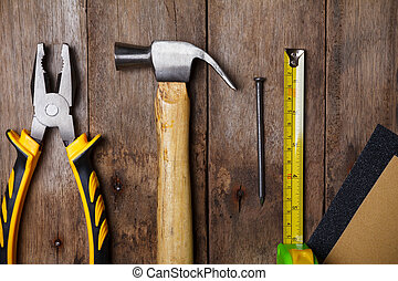 Sandpaper, pliers, measuring tape, hammer and nail on wooden...