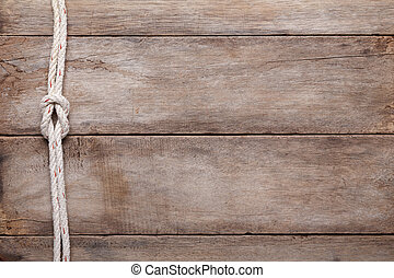 Weathered wooden table background with rope reef knot, top...