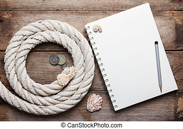 Blank open notebook and sea rope with ancient coins, on wooden background