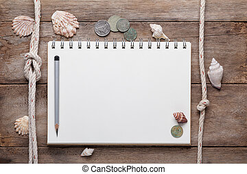 Weathered wooden table with blank notepad, coins and shells