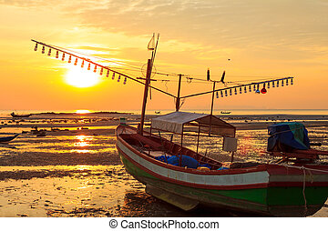 Old fishermans boat at sunset, during sea ebb