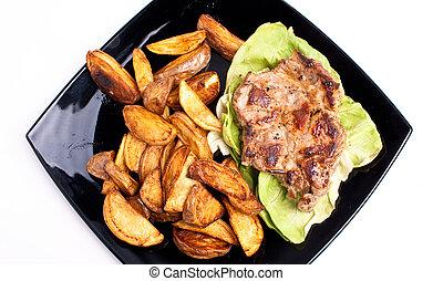 BBQ - Pork and fried potatos on black plate