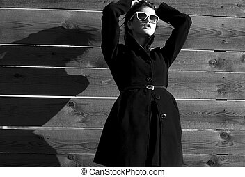 girl in a black coat against wooden fence