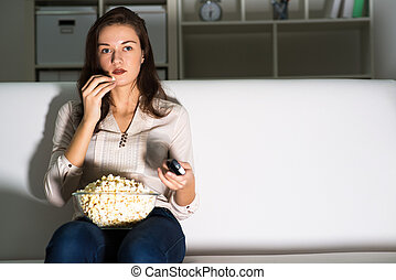 young woman watching TV - Young woman watching TV on the...