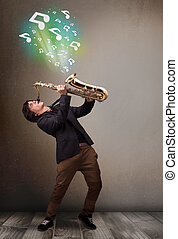 Attractive young musician playing on saxophone while musical...