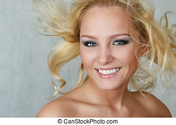 Attractive woman with fly-away hair isolated over white...
