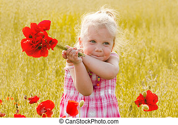 Beautiful little girl with a bouquet of red flowers stands...
