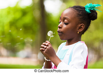 Outdoor portrait of a cute young black girl blowing a...