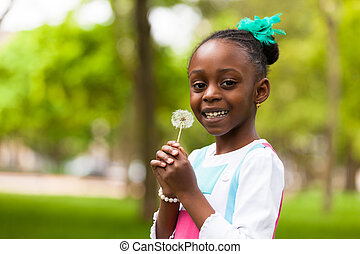 Outdoor portrait of a cute young black girl holding a...