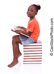 Cute black african american little girl reading a book,...
