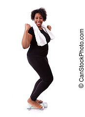African American woman cheering on scale - African people -...