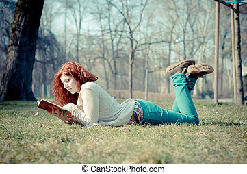 beautiful red head young woman reading book in the park