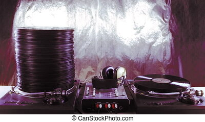 a large pile of records grows and shrinks on two dj...