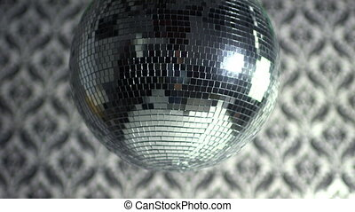 a funky discoball spinning with retro wallpaper background....