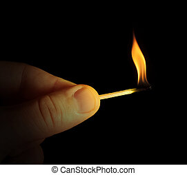 Hand holding burning match stick. Black isolated
