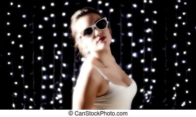 a sexy woman dances in front of disco lights