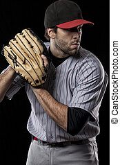 Baseball Player pitching a ball on a black background Studio...