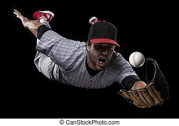 Baseball Player catching a ball on a black background....
