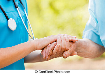 Caring for Elderly - Doctor or nurse holding elderly ladys...