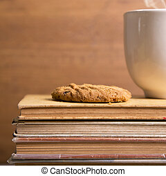 Coffee and cookies on top of books