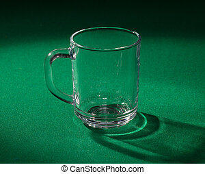 Empty glass beaker on green background
