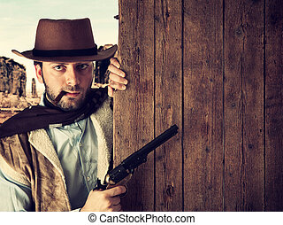 Bad gunman indicates with the gun a wooden plank - Bad...