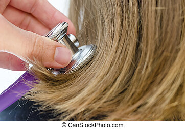 Damaged hair - Male hand holding stethoscope on damaged...