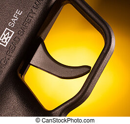 Trigger - Metal trigger on a rifle that has a yellow...